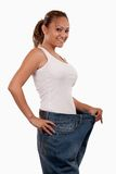 Weight loss. Attractive slim Asian woman smiling demonstrating weight loss by wearing an old pair of jeans and holding out to show how big the pants are Royalty Free Stock Images