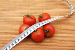 Weight Loss. Five ripe tomatoes with measuring tape sitting on a  wooden background, weight loss Royalty Free Stock Image