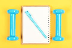 Weight loss and active lifestyle. Notebook, pen and gym equipment stock photos