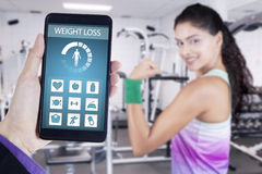 Weight loss app and healthy woman shows bicep. Image of hand holding smartphone with weight loss application and background of healthy woman showing her bicep at Stock Photo