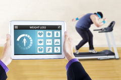 Weight loss app with man doing workout. Image of weight loss applications on the digital tablet screen with overweight person doing workout on treadmill Royalty Free Stock Image