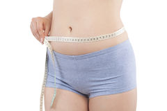 Weight loss. Beautiful caucasian girl measuring her hips with tape measure isolated on white background. Aesthetic medicine, weight loss and plastic surgery Stock Images