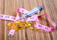 Weight loss. Capsules with measuring tapes on wooden background Stock Photo
