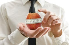 Weight loss coach. Closeup of weight loss coach pointing to apple wrapped with measuring tape in interface Stock Photos
