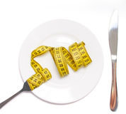 Weight loss concept. Plate with a knife and fork with twirled tape Stock Photos