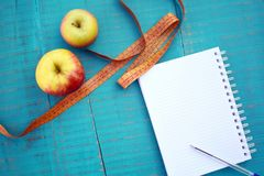 Weight loss concept. Apples, measuring tape and blank notebook on wooden background Royalty Free Stock Photography