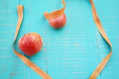 Weight loss concept. Apples and measuring tape on wooden background Stock Photos