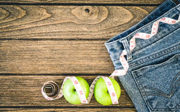 Weight loss concept, Blue jeans, green apples and measuring tape Royalty Free Stock Photo
