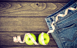 Weight loss concept, Blue jeans, green apples and measuring tape Royalty Free Stock Images