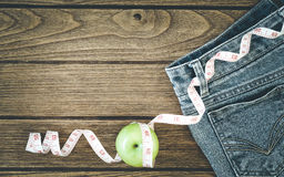 Weight loss concept, Blue jeans, green apples and measuring tape Stock Images