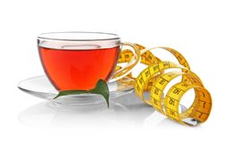 Weight loss concept. Cup of tea and measuring tape isolated. On white royalty free stock image