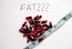 Weight loss concept with fat burner pills and a measuring tape Royalty Free Stock Photos