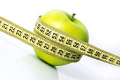 Weight loss concept. Green apple with a measure tape diagonal Royalty Free Stock Image