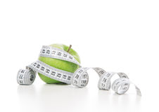 Weight loss concept green apple and tape measure stock photo