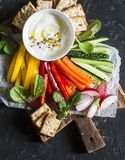 Weight loss concept of a healthy diet food. Mix vegetables and greek yogurt sauce on a wooden rustic cutting board. Sweet pepper,. Carrot, cucumber, radish and royalty free stock image
