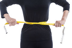 Weight loss concept, the woman in black tries to reduce her wais Royalty Free Stock Photo