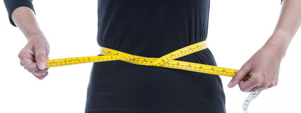 Weight loss concept, the woman in black tries to reduce her wais Stock Photo