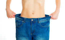 Weight loss concept. Woman wearing old jeans. Isolated on white Royalty Free Stock Image