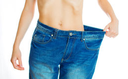 Weight loss concept. Woman wearing old jeans. Isolated on white Stock Photography