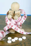 Weight loss concept with wooden man wrapped in a measuring tape and diet pills Royalty Free Stock Image