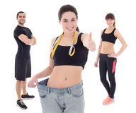 Weight loss concept - young woman after diet with her trainers i Royalty Free Stock Photo