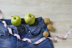Weight loss diet with apples for jeans. Weight loss diet with: green apples, nuts and measure tape on the small jeans Royalty Free Stock Images