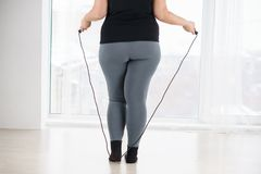 Overweight woman with jumping rope cardio workout. Weight loss, endurance, jump-fit, vitality, active lifestyle. overweight woman with jumping rope cardio royalty free stock images