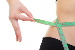 Weight loss. Green measuring tape on woman body Stock Photography