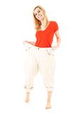 Weight loss - happy woman in too big trousers Stock Photo