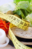 Weight loss, healthy diet. Tape measure over the salad vegetables, diet concept and a balanced diet and healthy royalty free stock photography