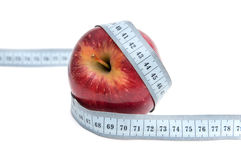 Weight loss and healthy dieting. Red apple with measuring tape isolated on a white background Royalty Free Stock Photo