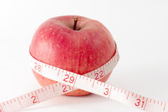 Weight loss and healthy dieting. Red  apple with measuring tape and water drops. Weight loss series Royalty Free Stock Images