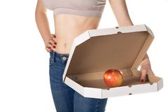 Weight loss and healthy eating or dieting concept. Slim girl with open pizza box and red apple in it. stock images