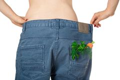Weight loss and healthy eating or dieting concept. Slim girl in oversized jeans with a carrot, dill and parsley in the pocket royalty free stock images