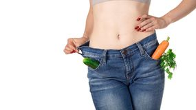 Weight loss and healthy eating or dieting concept. Slim girl in oversized jeans with raw vegetables in the pockets. stock photography
