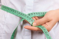 Weight Loss and Healthy Lifestyle Concept. Fitness Woman Measuri. Ng Her Waistline with Measure Tape extreme closeup Stock Photos