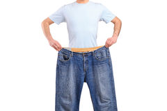 Weight loss male showing his old jeans. Isolated on white Royalty Free Stock Image