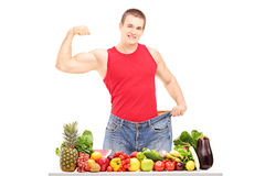 Weight loss man showing his muscles and standing behind a pile o Royalty Free Stock Photos