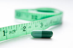 Weight loss pill. Pill and measuring tape in close up mode stock image