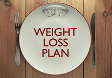 Weight loss plan. Printed on a plate with bathroom scales Stock Image