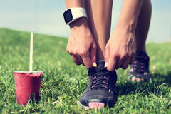 Weight loss - runner tying laces with smoothie Stock Photo