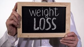 Weight loss text on blackboard in doctor hands, healthy diet recommendations. Stock footage royalty free stock photography