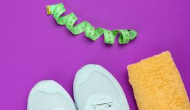 Weight loss. Training concept. Sport shoes, towel, ruller on a purple background. Top view stock photo