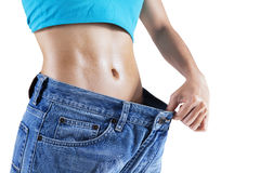 Weight Loss Woman. Weight loss concept: Slim woman pulling oversized jeans Royalty Free Stock Photo