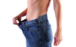Weight loss woman concept. Young healthy woman in big jeans showing weight loss Stock Photos