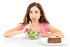 Weight loss woman eating salad wishing for a piece of cake. Woman on diet looking unhappy when eating salad and yearning for a piece of cake. Isolated on white Stock Images