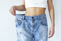 Weight loss woman with jean on gray background royalty free stock images