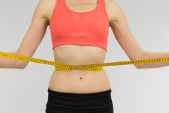 Weight loss woman with a measurement tape. Woman holding a measurement tape around the belly on grey background Stock Images