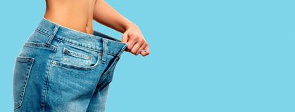 Weight loss. Woman in oversize jeans on blue background. Diet concept and weight loss. Woman in oversize jeans on blue background Royalty Free Stock Image