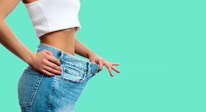 Weight loss. Woman in oversize jeans on green background. Diet concept and weight loss. Woman in oversize jeans on pastel green background Stock Photo